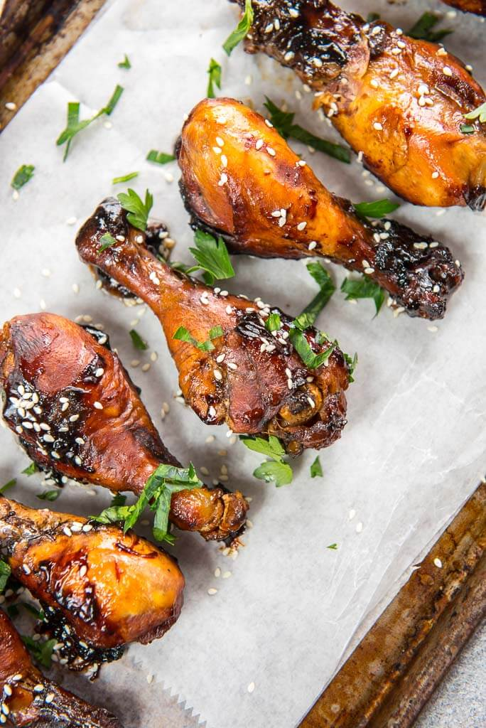slow cooker sticky chicken drumsticks on parchment paper on cookie sheet
