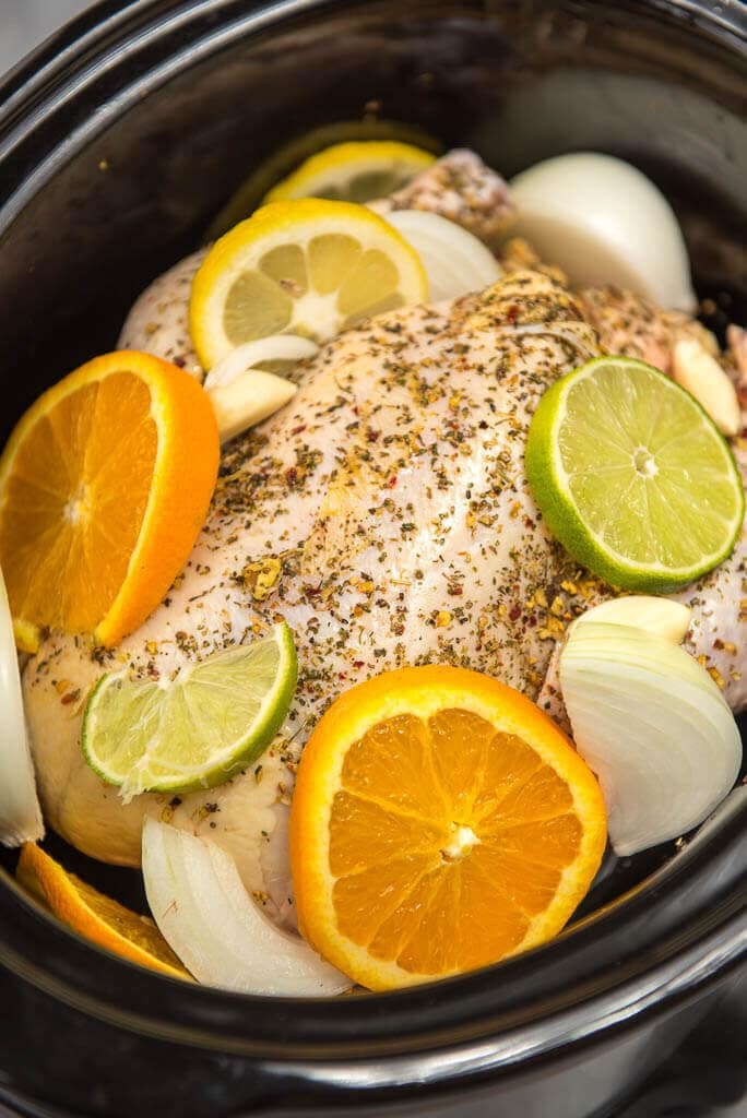 Whole chicken in black crock pot seasoned with herbs and covered on the sides with lemon and lime wedges, onions and garlic.