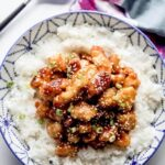 honey crispy chicken over white rice in a blue and white bowl with purple napkin and serving spoon