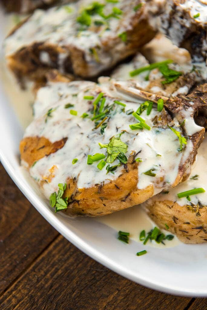 Slow Cooker Pork Chops are always a family favorite. This bone in version includes a Creamy Herb Sauce that takes it over the top in flavor!