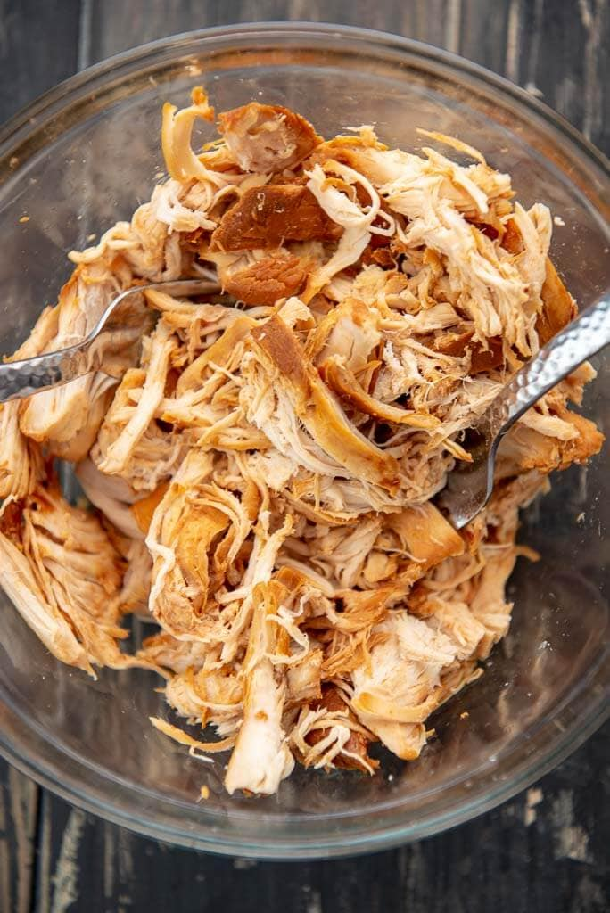shredded chicken with forks in a glass bowl for pulled chicken