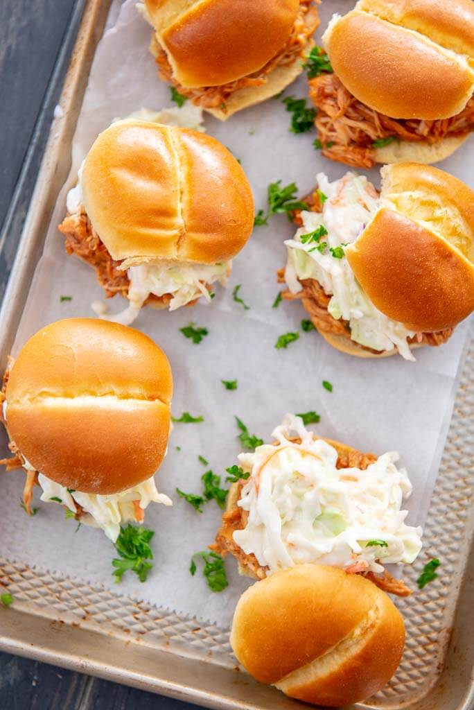 tray Slow Cooker BBQ Pulled Chicken sandwiches on Hawaiian slider bun topped with coleslaw