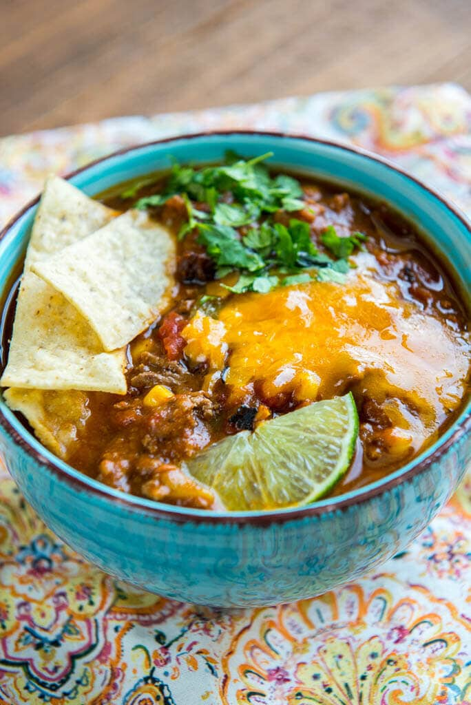 Slow Cooker Taco Soup is a family favorite dinner that has just a few ingredients and can be made in minutes. My secret ingredients makes it the best taco soup out there for flavor and richness!