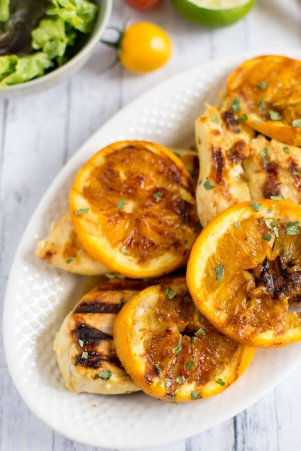 Mustard Citrus Chicken on a white platter with oranges