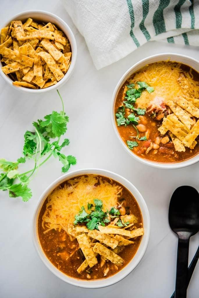 slow cooker spicy chicken enchilada soup in white bowls topped with tortilla strips and cilantro