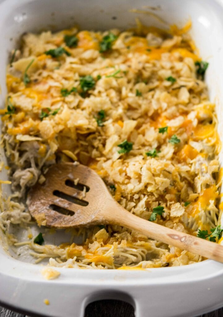 Slow Cooker Chicken Noodle Casserole in a white slow cooker with a brown serving spoon resting not the side.
