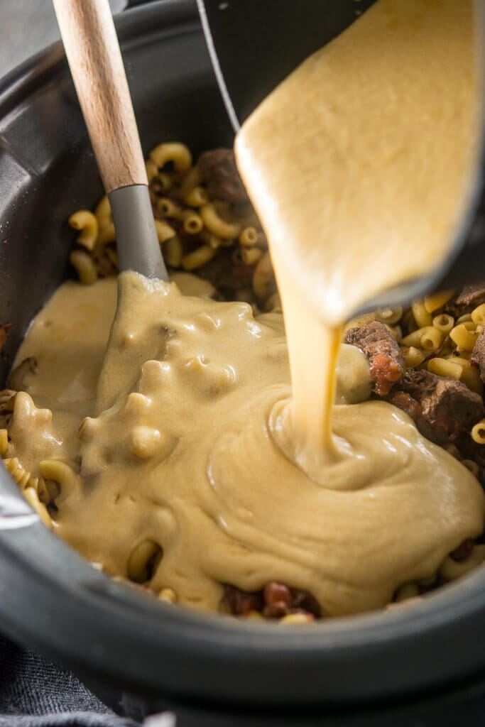 Pouring the cheese sauce into the noodles and beef to make Slow Cooker Beer Mac & Cheese