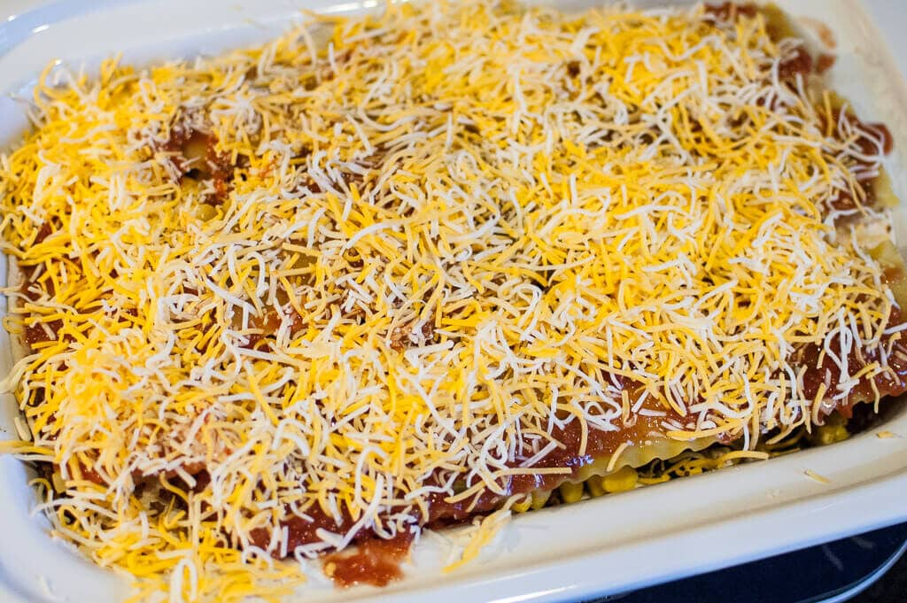 Pre-cooked Slow Cooker Mexican Lasagna, topped with shredded cheese in a white crock.