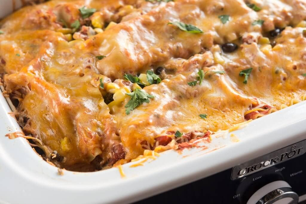 Slow Cooker Mexican Lasagna topped with melted cheese in a casserole slow cooker.