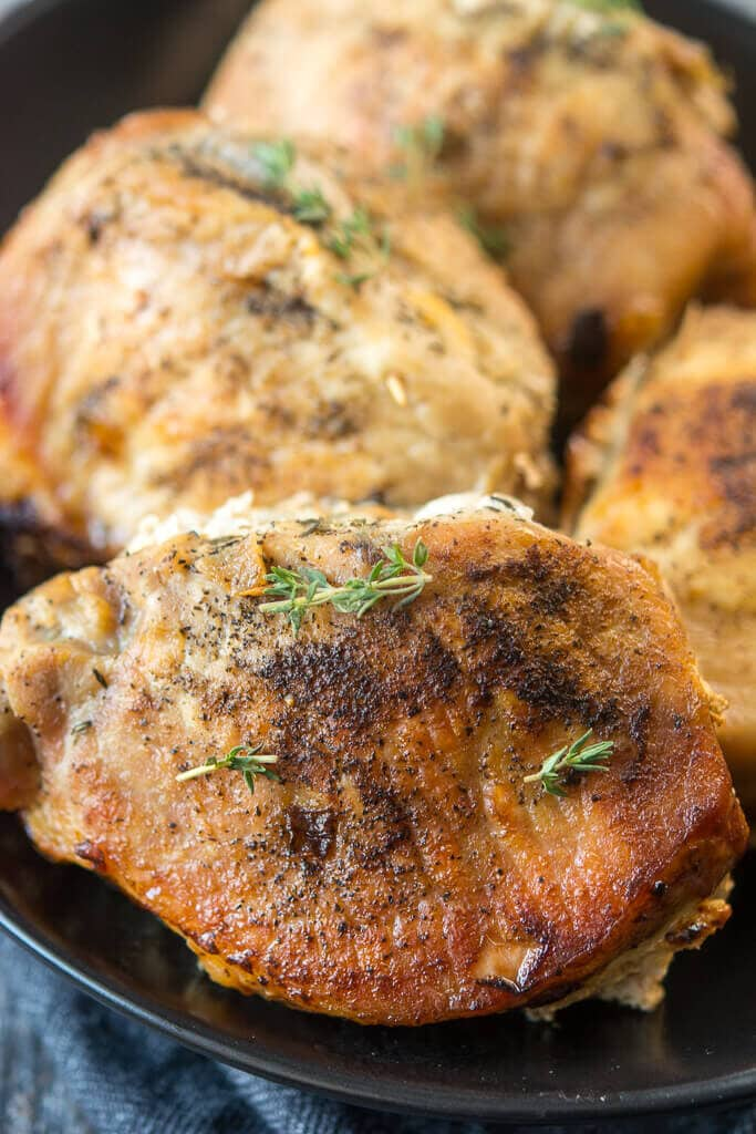 Up close picture of Slow Cooker Stuffed Pork Chops on a black plate