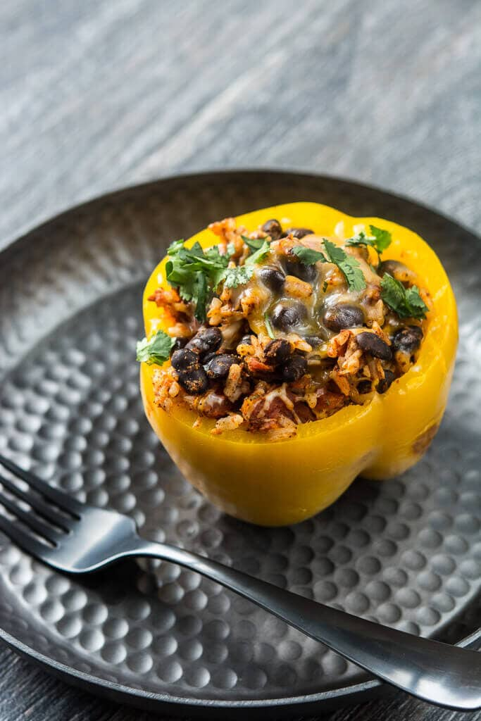 Overhead picture of slow cooker stuffed pepper with a sprinkle of cilantro on a black plate with a black fork resting on the side.