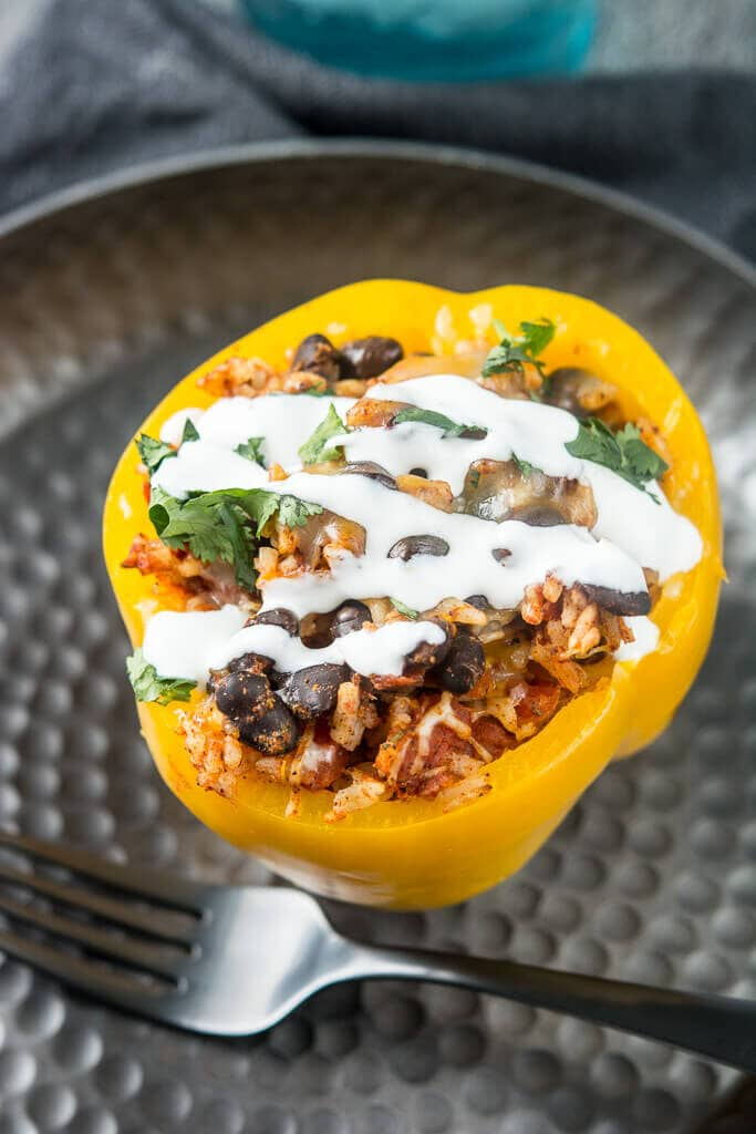 Overhead picture of slow cooker stuffed pepper with a drizzle of sour cream and a sprinkle of cilantro on a black plate with a black fork resting on the side.