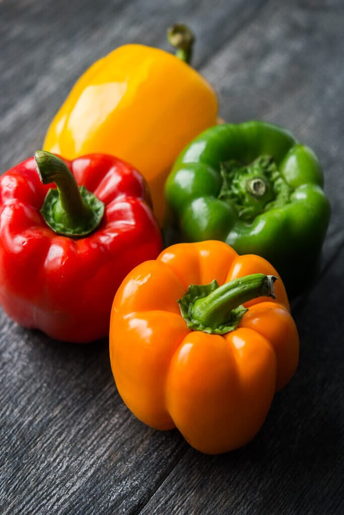 a picture of red, yellow, orange and green bell peppers