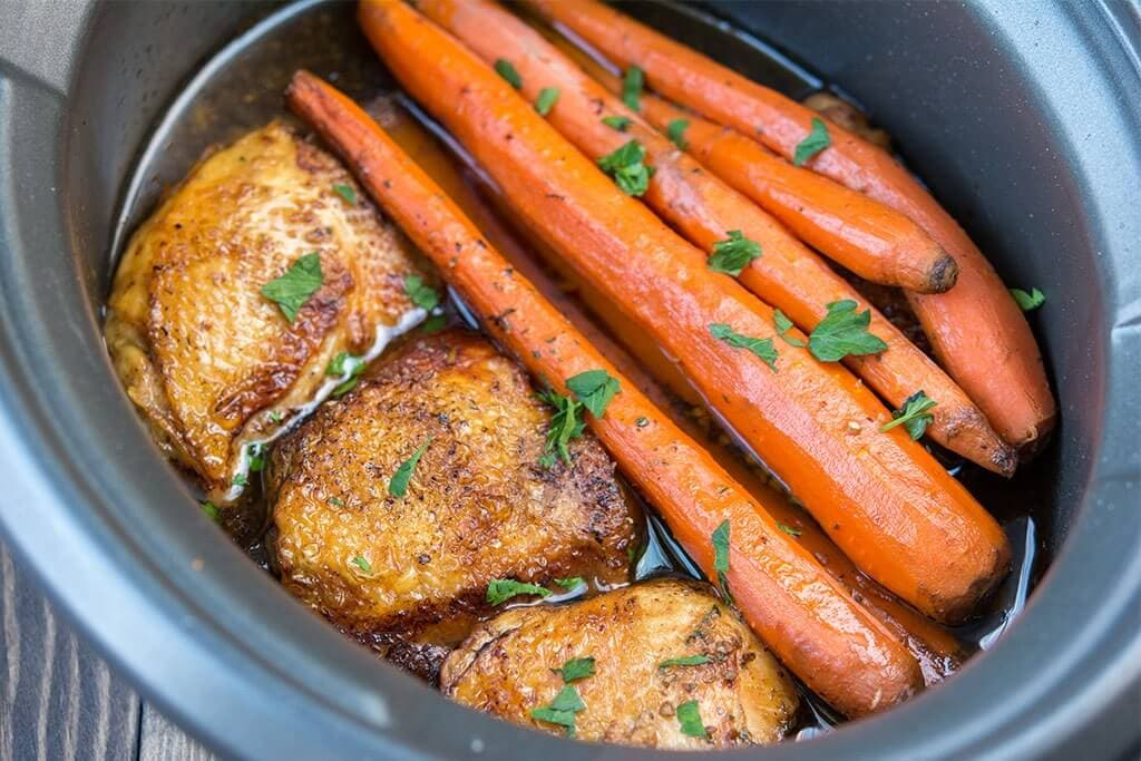 Slow Cooker Balsamic Chicken with Carrots sprinkled with parsley, presented in a black crock