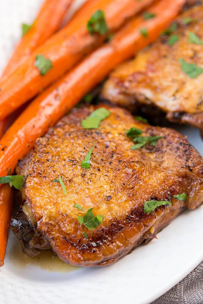 Slow Cooker Balsamic Chicken with Carrots sprinkled with cilantro resting on a white plate.