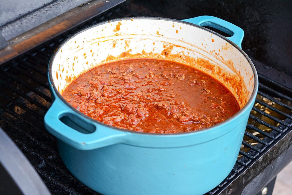Slow Cooker Tailgate Chili in a blue dutch oven heating on the grill