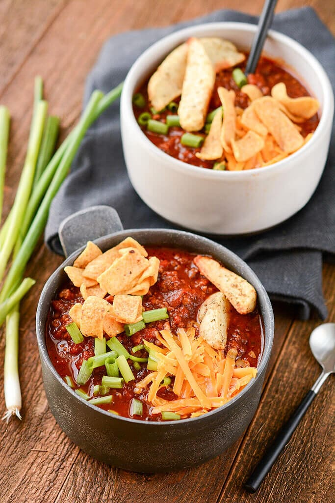 Slow Cooker Tailgate Chili in a metal bowl topped with cheese chips and onions