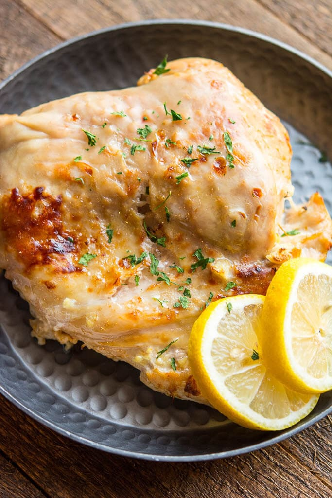 Cooked Slow Cooker Turkey Breast overhead shot on black plate with lemons