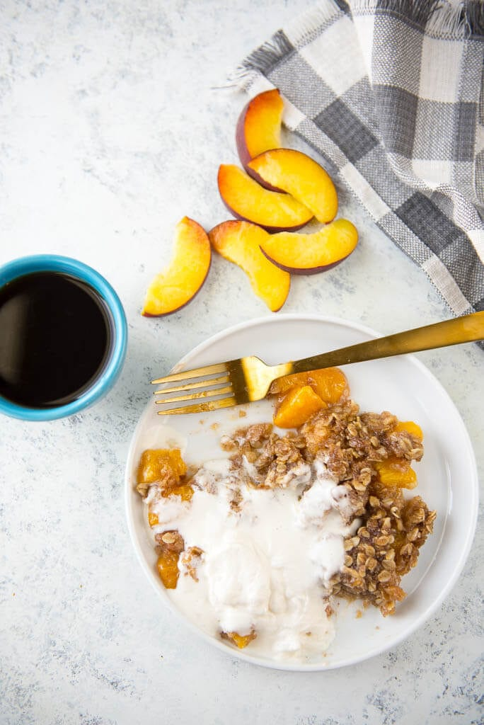 Looking for a delicious treat to use all those farmer's market fresh peaches? Slow Cooker Peach Cobbler with Fresh Peaches and the most delicious Yogurt Whipped Cream is the perfect summer dessert!