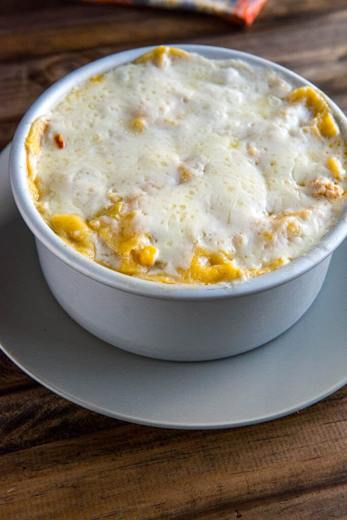 Silver pan on a silver plate of cooked chicken enchilada casserole with melted cheese on top.