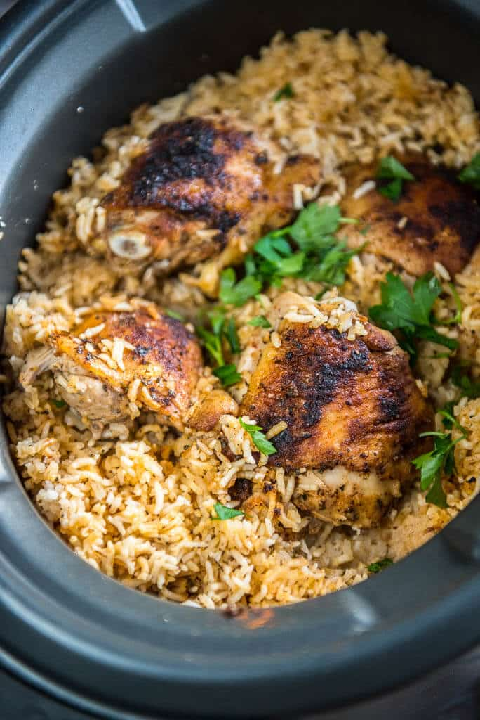 Slow Cooker Baked Chicken Thighs with Rice garnished with greens in slow cooker