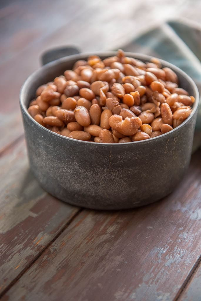 Slow Cooker Pinto Beans in metal bowl on painted table