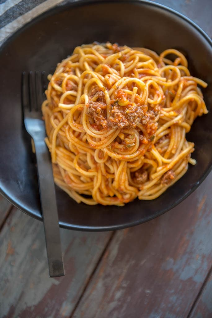 Veggie Packed Instant Pot Spaghetti with Meat Sauce piled on a black plate
