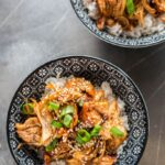Slow Cooker Teriyaki Chicken in black and white bowls topped with green onion