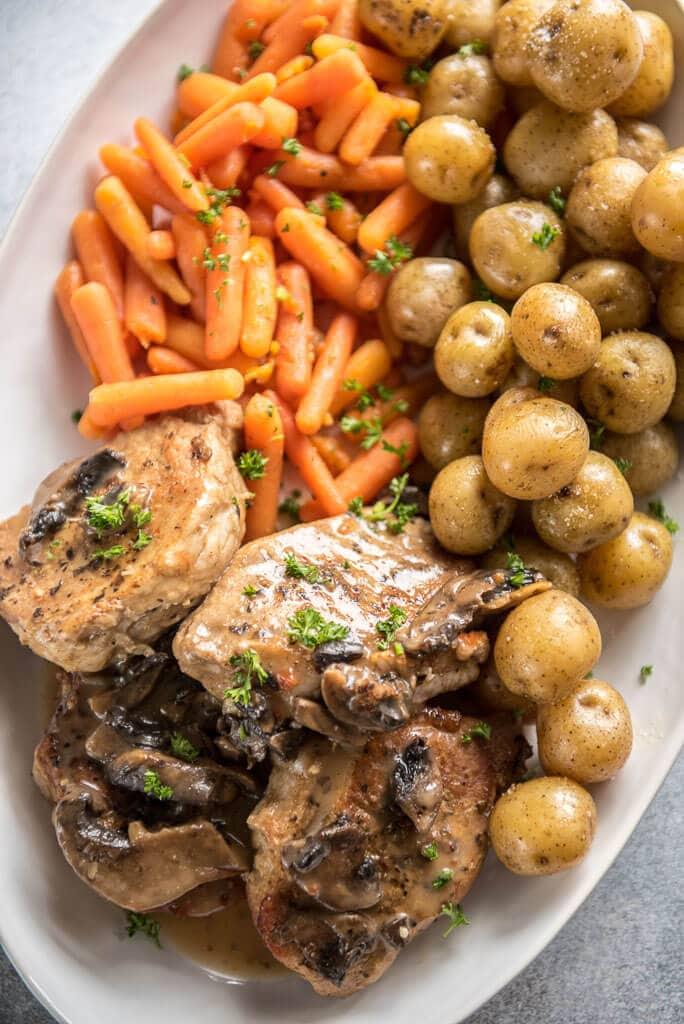 Instant Pot Pork Chops with Mushroom Gravy on white platter with whole baby potatoes and carrots
