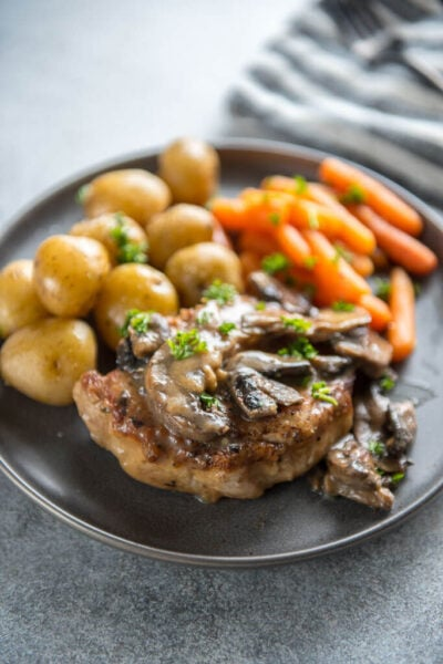 Instant Pot Pork Chops with Mushroom Gravy on round gray plate with whole baby potatoes and carrots