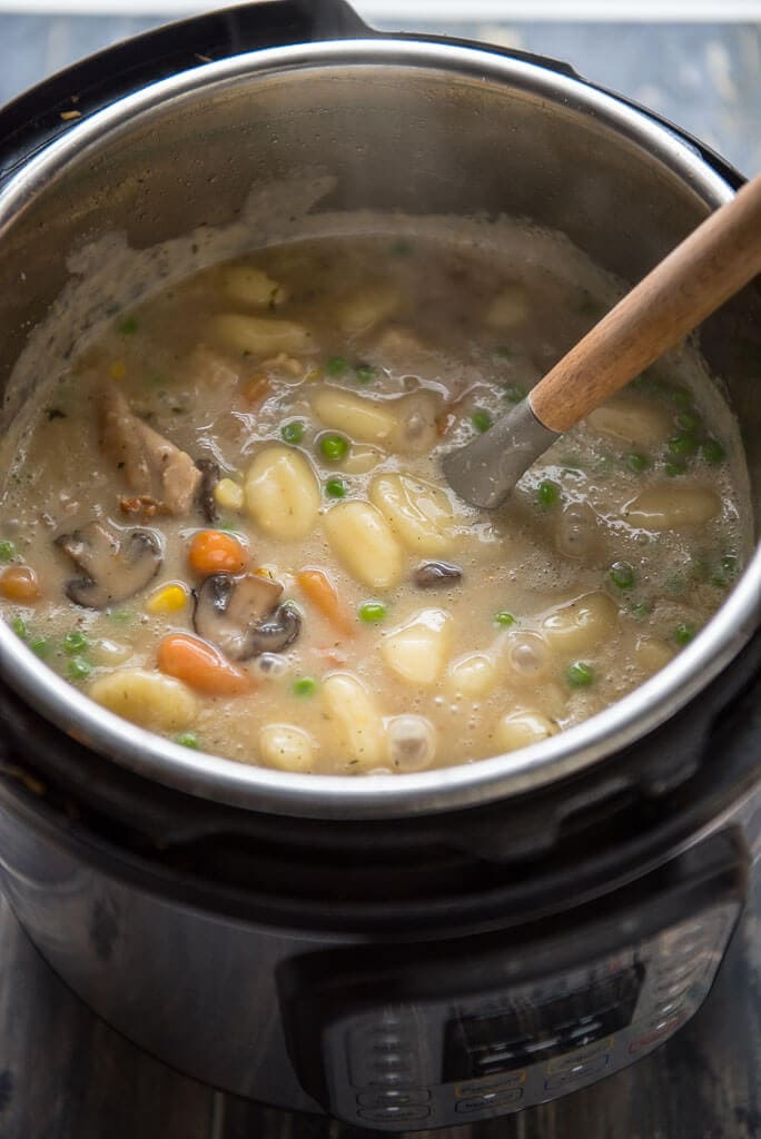 chicken and dumplings in Instant pot with ladle for serving