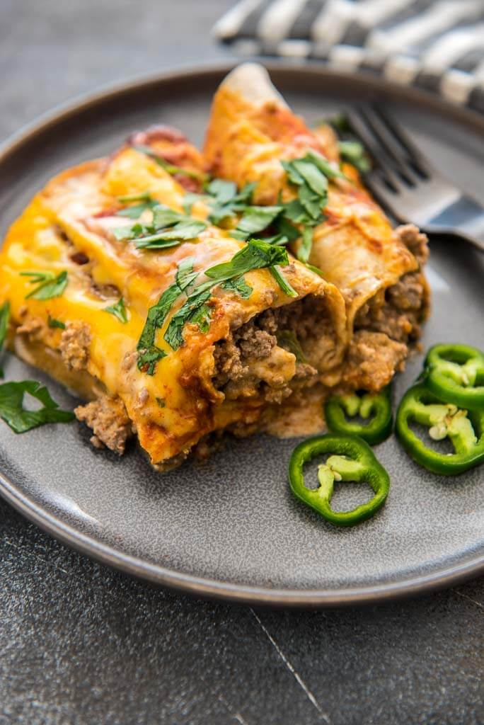 slow cooker enchiladas on gray plate with sliced jalapeños