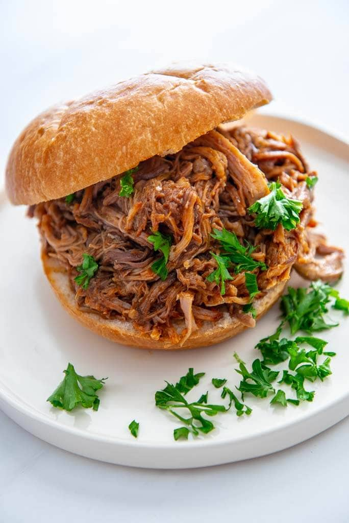 low cooker bbq pulled pork on a kaiser roll on a white plate with parsley garnish