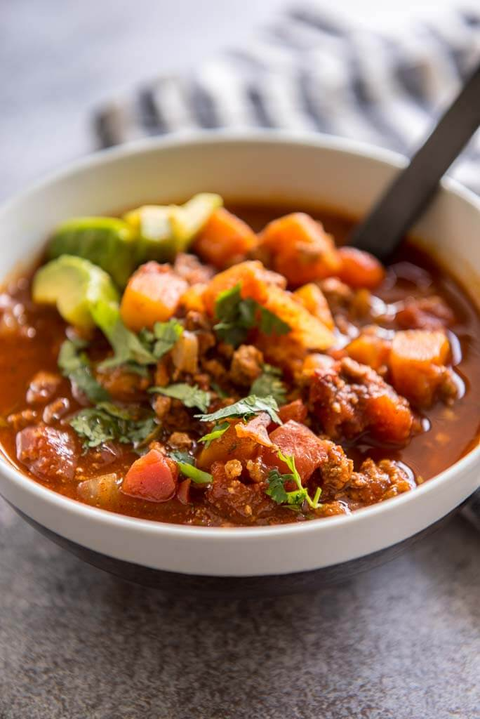 slow cooker turkey chili in a white bowl with a black spoon