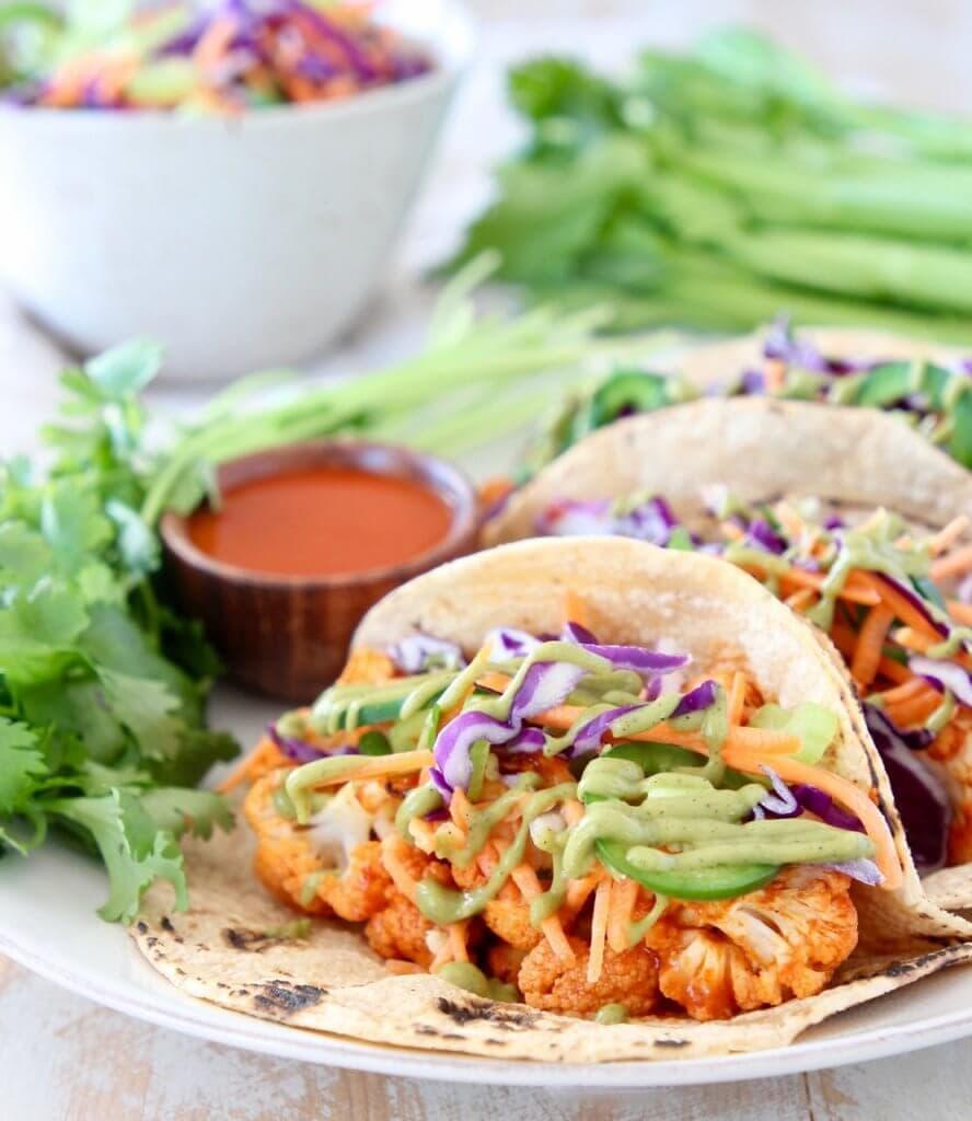buffalo cauliflower tacos on a platter with slaw