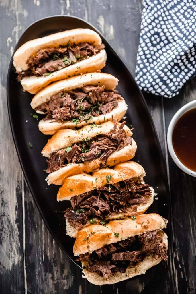 5 French dip sliders on mini rolls on a black platter with a side of au jus