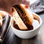 hand holding French dip into au jus sauce in white bowl