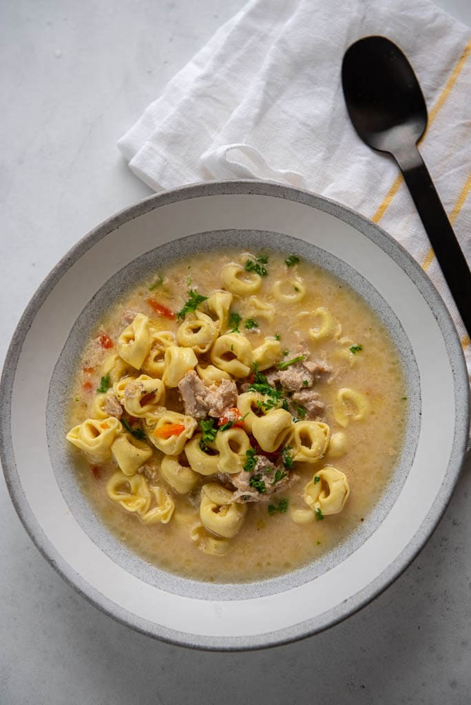 chicken tortellini soup in gray bowl next to spoon and yellow striped napkin