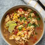 gray bowl full of spicy chicken soup topped with cilantro