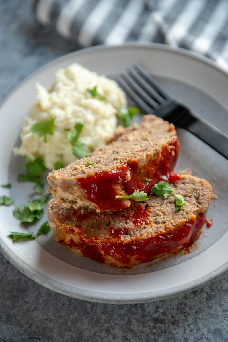 2 slices of turkey meatloaf on a gray plate with mashed cauliflower
