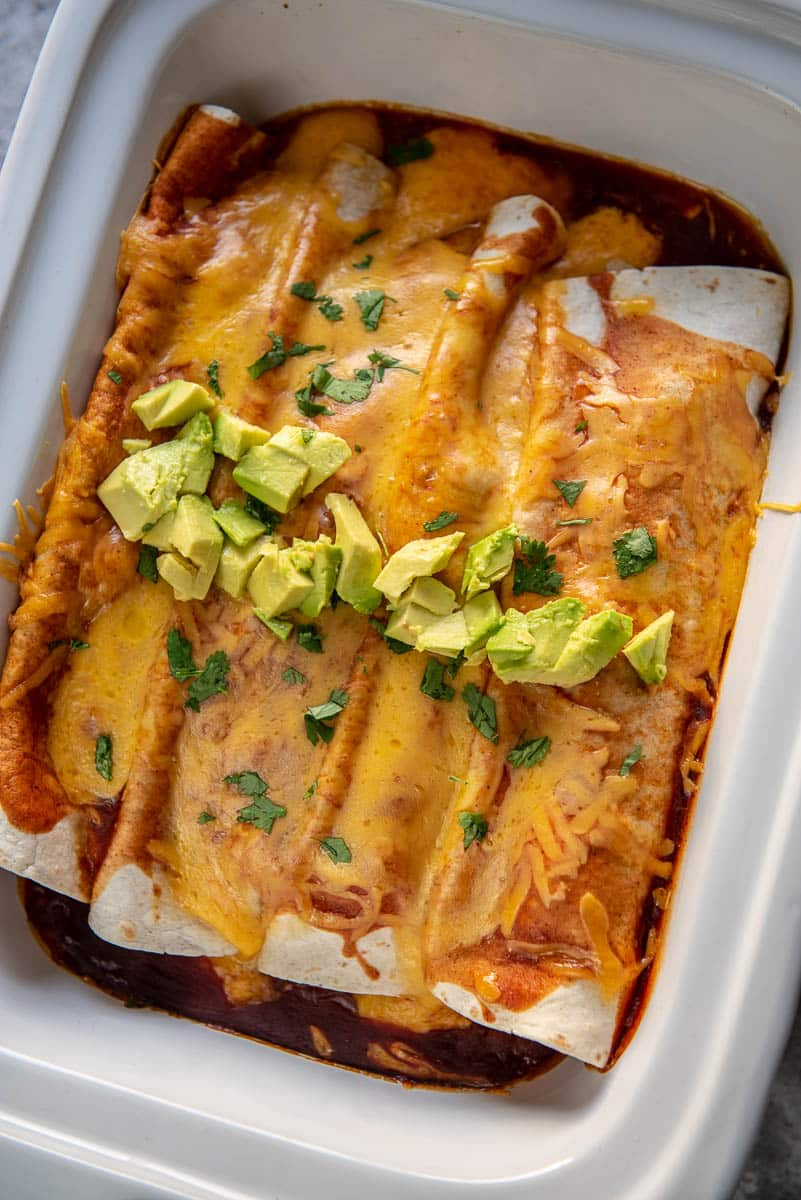 butternut squash enchiladas topped with avocado in a casserole slow cooker