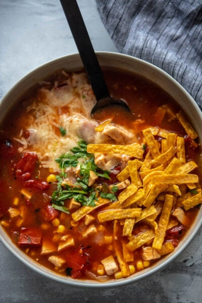 gray bowl of chicken tortilla soup topped with tortilla strips, melted cheese and cilantro