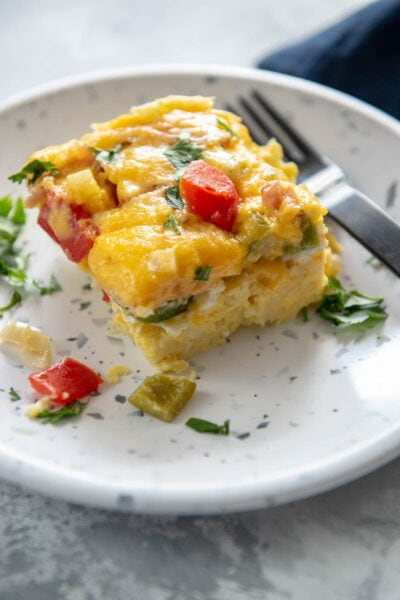 square slice of Denver omelette casserole on a white with blue speckles plate