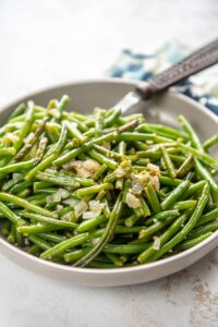 sauteed green beans with garlic in a bowl with fork