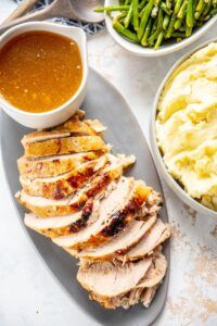 sliced turkey breast on gray platter with gravy and sides of mashed potatoes and green beans