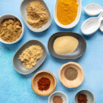 tiny bowls filled with spices to make curry seasoning on a blue backdrop